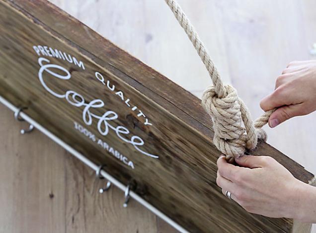 8. Skrze vrchní otvory provlečte provaz aozdobně ho na koncích uvažte. Na věšák zavěste háčky ašálky.