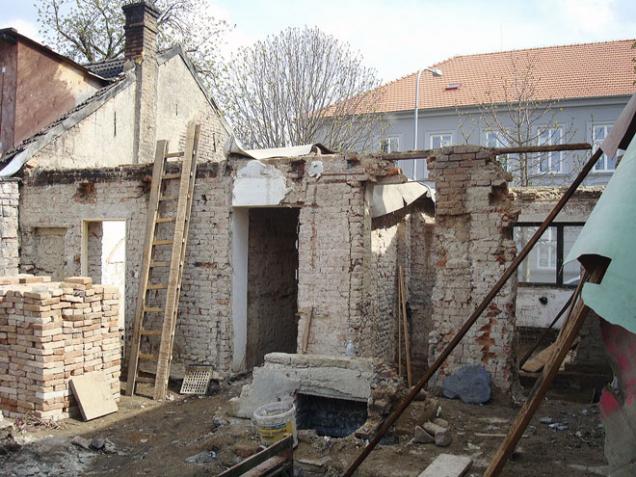 Torzo domu vzávěru bouracích prací. Vlevé části jsou vidět vyskládané očištěné cihly, které jsme následně využili navyzdění stěn vpřízemí.