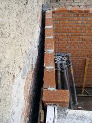 Vyzděná stěna skladu na hranici pozemku a zcela zbytečná ztráta podlažní plochy, způsobená odsazením zdiva od sousedního domu.