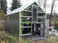 Dvoupodlažní montovaný RD vpasivním standardu (senergetickým štítkem A) sestávající ze stavebních komponentů Lindab od konstrukce domu přes fasádu až po střechu aokapové systémy. Na primární rámovou ocelovou konstrukci je zavěšen kompaktní sendvičový plášť pomocí sekundární konstrukce ztenkostěnných profilů. Obvodové stěny astřešní plášť jsou izolovány vnějším sendvičovým PIR panelem tl. 100mm aminerální vlnou tl. 200mm. Sendvičovou skladbu uzavírá rošt zlehkých profilů Lindab asádrovláknité desky. Vnější fasádu domu tvoří přímo vnější profilovaný plech PIR panelu spolyesterovou úpravou. Dům má pasivní plastová okna (šestikomorový 85mm profil) sizolačním trojsklem Ug = 0,5/0,6 W/m2K.