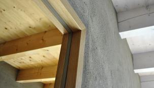 Detailní pohled narámovou zárubeň, která zobou stran lícuje stenkou hrázděnou příčkou shrubou hliněnou omítkou. Vlevo je přirozená barevnost smrkového stropu, vpravo je strop nabělen voskovým nátěrem spigmentem.