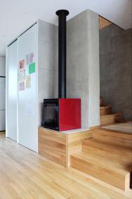 Propojení podlahy, schodiště iboxu nadřevo dojednoho celku. Navšech prvcích je jako finální povrch použita stejná dubová podlahová krytina.