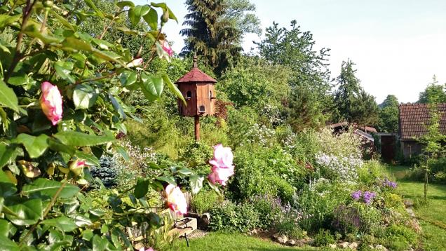 Bylinkové atrvalkové záhony vpozadí se stylovým dřevěným holubníkem, který podtrhuje ryze venkovský ráz zahrady.