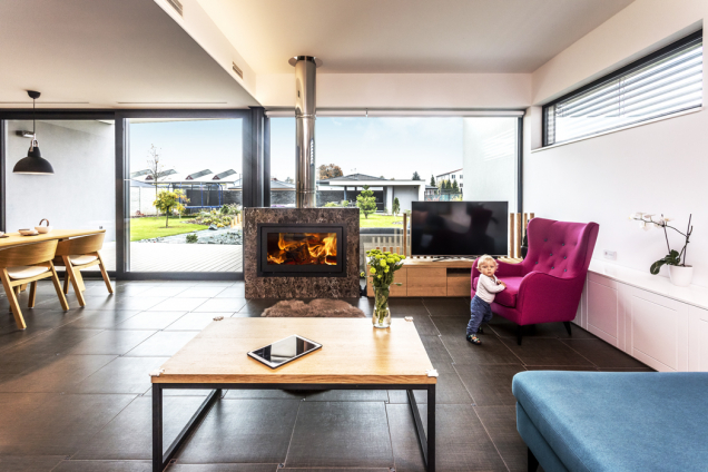 Obývací pokoj je díky posuvnému prosklení otevřen dozahrady. Hranici pozemku uzavírá objekt se saunou aletní kuchyní.