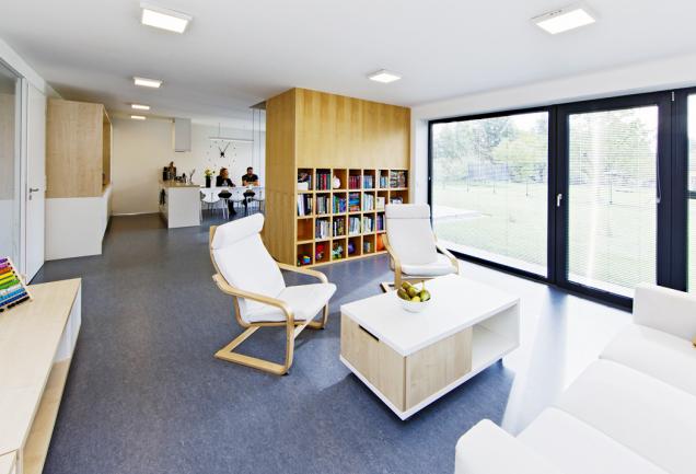 Těleso uprostřed společné obývací části spojuje atypické schodiště sobývací stěnou aknihovnou. Slouží jako originální solitér azároveň šetří místo (návrh Ateliér 38)