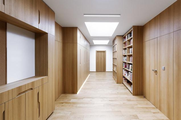 Chodba nemusí být nevzhledný tmavý prostor. Zde slouží jako víceúčelová hala s úložnými prostory, knihovnou a hernou pro děti, shora ji krásně osvětluje střešní okno (návrh Ing. arch. Aneta Stružková)