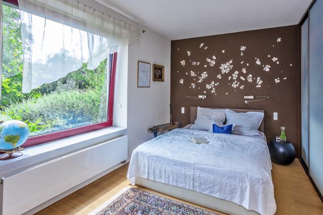 Stěna v záhlaví postele je obložená mušlemi z cest. Spolu s dalšími textiliemi v ložnici je dokladem výtvarného talentu paní domu.
