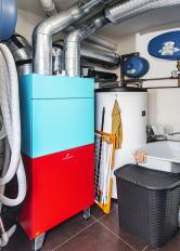 Vtechnické místnosti je uložena kompaktní jednotka Drexel aWeis X2 svýkonem 3,2 kW. Jednotka obsahuje malé tepelné čerpadlo se zemním kolektorem avzduchotechnickou jednotku srekuperací, vedle je nádoba nateplou vodu.