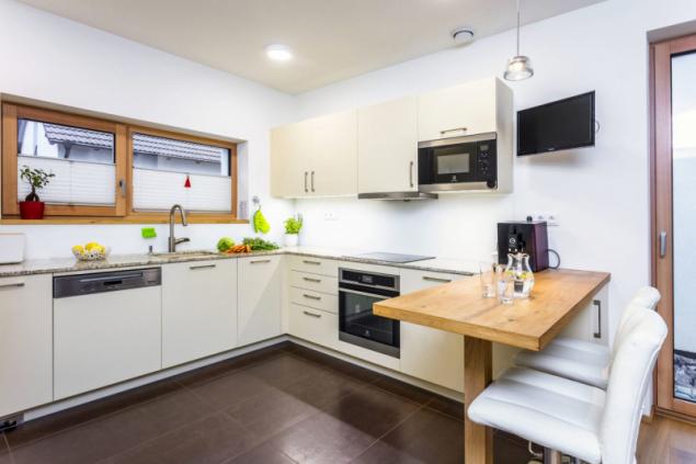 Rohová kuchyň s příručním barovým stolkem a dvěma barovými křesílky