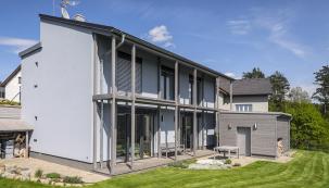 Rodinný dům postavený ze zdicího systému Ytong. Zosluněné strany kryje fasádu konstrukce spojená spřesahem střechy anesoucí lamelový rošt nad přízemím, prosklené plochy lze efektivně zastínit ipomocí venkovních rolet.