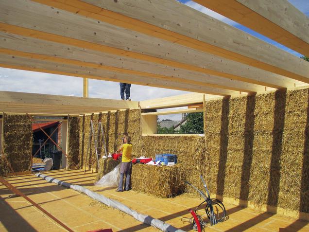 Stavba pasivního domu vDobřejovicích uPrahy. Obálku domu tvoří balíky, vyrobené přímo napoli. Kpozitivní energetické bilanci přispívá iprosklená jižní stěna avegetační střecha.