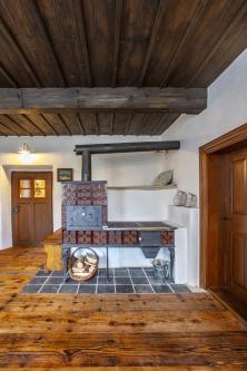 Načernou kuchyni vevedlejší místnosti navazuje kachlový sporák azděná pec. Dalším zdrojem tepla, který se stará mimo jiné otemperování domu, je plynový kotel ateplovodní podlahové topení aradiátory.