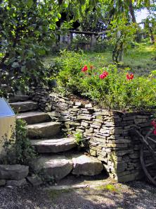 Kamenné schody přesně navazují astylově doplňují kamenné zídky aspolu srostlinami vytvářejí malebná zákoutí avýškově člení zahradu.