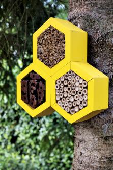 Včelí domeček zdílny Hammer vbarevném akcentu žluté. Stejná barva se opakuje inapumpě ahoupačkách.