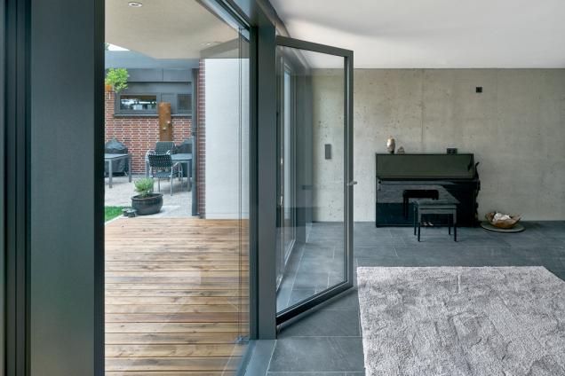 Fasáda tvořená prosklenými panely na výšku celé místnosti, které zahrnují i velkoformátové otvíravé části, umožňuje splynutí interiéru s venkovním prostorem (Schüco AWS 35 PD.SI). (Zdroj: Schüco CZ / Christian Eblenkamp)