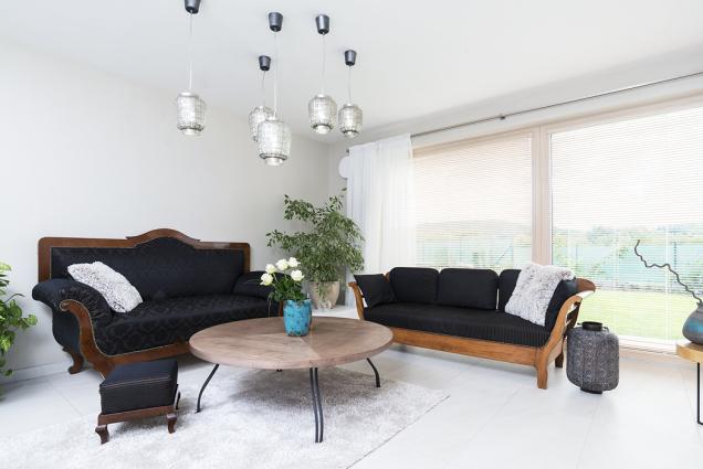 Obývací pokoj má díky velké rohové prosklené ploše panoramatický výhled a bohatou záplavu světla. Historické sofa působí v moderním domě velmi půvabně.