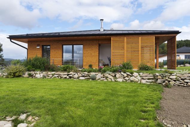Architektonicky zajímavým a velmi praktickým prvkem jsou posuvné dřevěné fasádní panely. Lze je přemístit podle potřeby a vytvořit tak na terase pod přesahující střechou zákoutí chráněné před sluncem či větrem.
