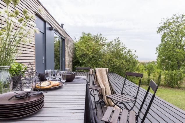 Navýchodní terase zmodřínového dřeva kralují velký jídelní stůl (Ikea) astaré těžké skládací židličky, které architektku provázejí oddětství.