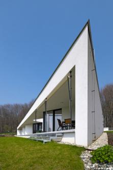 Z přilehlé cesty snad může tento neobvyklý bungalov vypadat jako obyčejný kvádrový domek – dokud nevstoupíte na zahradu a nepohlédnete na jeho zkosenou třetí stěnu. Dynamický trojúhelníkový tvar vznikl díky snaze dostat do domu co nejvíce světla a slunce – přepona trojúhelníku je orientována přímo na jih