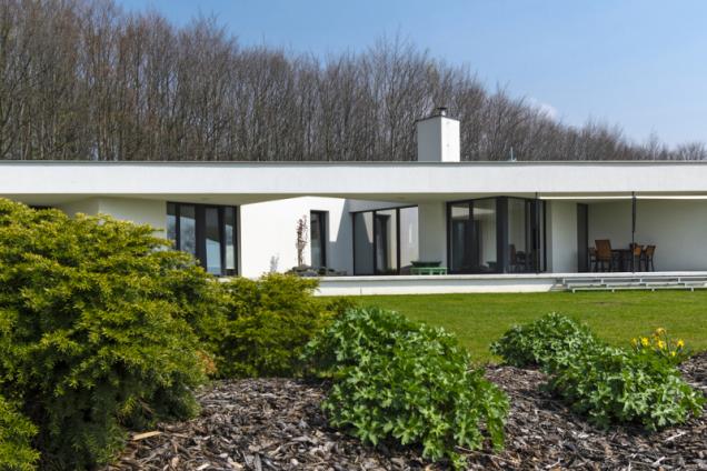 Pohled ze zahrady na terasu domu a hlavní obytné místnosti. Budova je mírně vyvýšena nad terénem, takže do zahrady se sestupuje po záměrně subtilních kovových schůdkách umístěných v dolní části patia
