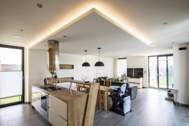 Vybavení kuchyně je laděno do světlých barev a prostor obývacího pokoje je opticky oddělen použitím nábytku tmavších barev, které kontrastují se zbytkem místnosti
