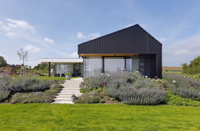 """Kompozici domu tvoří základní hmota se sedlovou střechou a na něj kolmá prosklená část s plochou střechou. Kontrast tvarů se pojí i s kontrastem materiálů a barev – masivní černá hmota versus subtilní skleněná """"přístavba"""" s bílou atikou"""