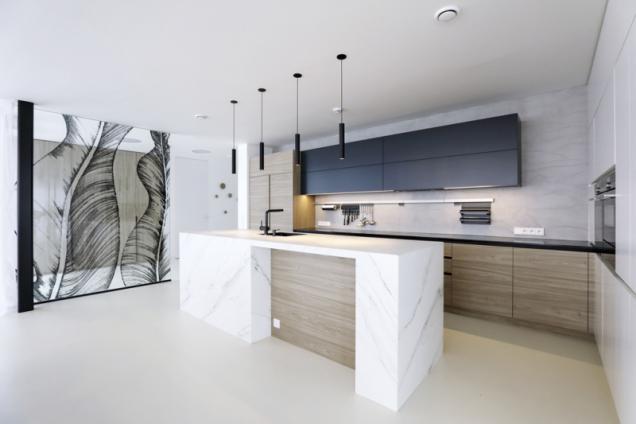 Kuchyň zdobí dělicí skleněná stěna s dekorativní fólií s figurálním motivem, který si majitelé domu sami vybrali. Kuchyňský ostrůvek vypadá jako vytesaný z bílého mramoru, ale jde o tenkostěnné tvrdé keramické desky vyrobené speciální technologií