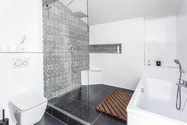 Koupelna v patře je neobvykle prostorná a pohodlná. Přispěl k tomu i nápad vytvořit stupínek s velkým sprchovým koutem, nikou a rohovým sedátkem