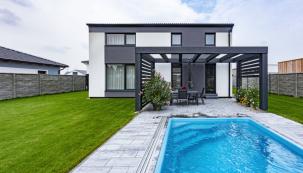 Elegantní kompaktní charakter domu zvýrazňuje kombinace bílé a šedé barvy, kterou dodržuje i dřevěná pergola mořená do šedého odstínu a betonová dlažba na terase