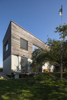 Plášť domu tvoří povrchově neošetřená modřínová prkna kladená horizontálně, která postupem času získávají přirozenou patinu. Ve†spodní části stavby jsou doplněna fasádními deskami Cembrit