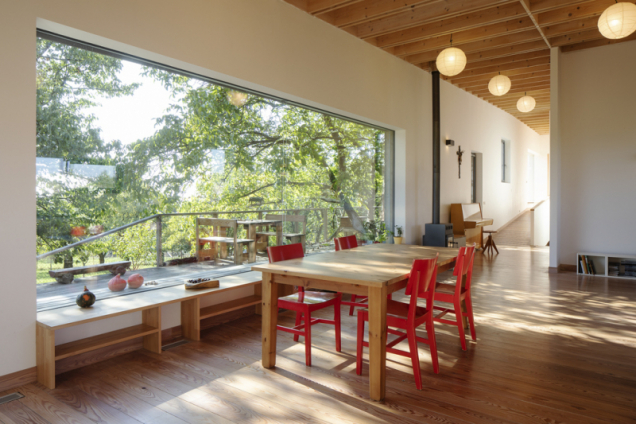 Umístění jídelního stolu lze považovat za ideální – krásný výhled do zeleně navozuje příjemnou atmosféru, odstíny dřeva v kombinaci s červenou barvou dodávají interiéru na útulnosti