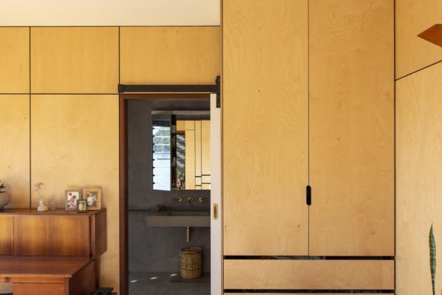 obložení stěn a vestavěný nábytek tvoří desky z překližky se světlou březovou dýhou. Přiznané spáry tvoří na stěně zajímavou geometrickou hru. Barevná škála použitá v interiéru odpovídá zlatavým a rezavým odstínům pláže a buše
