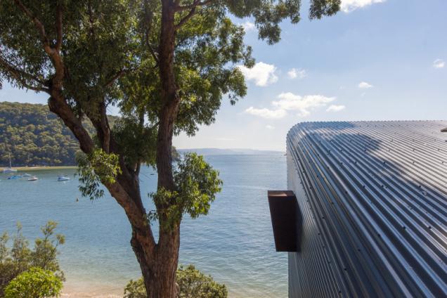 Boční okénko v hliníkovém plášti slouží k provětrávání společného obývacího prostoru. Široký lem z cortenového plechu jej chrání před deštěm a větrem. Žlábky v plechovém plášti mají mírný sklon, aby z nich odtékala dešťová voda