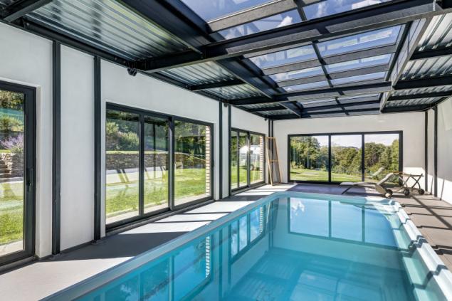 Majitelé rádi sportují, proto vznikla moderní přístavba s ocelovou nosnou konstrukcí a částečně prosklenou střechou pro krytý bazén. Velké plochy oken maximálně propojují interiér s okolím