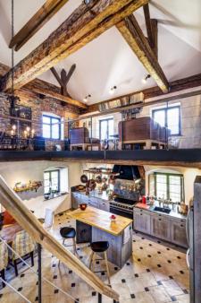 Centrem kuchyně je zakázkově vyrobený pracovní a zároveň barový ostrůvek s deskou ze starých trámů. Tu podpírá originální ocelová podnož. Kuchyňské skříňky dostaly záměrně patinovaný povrch