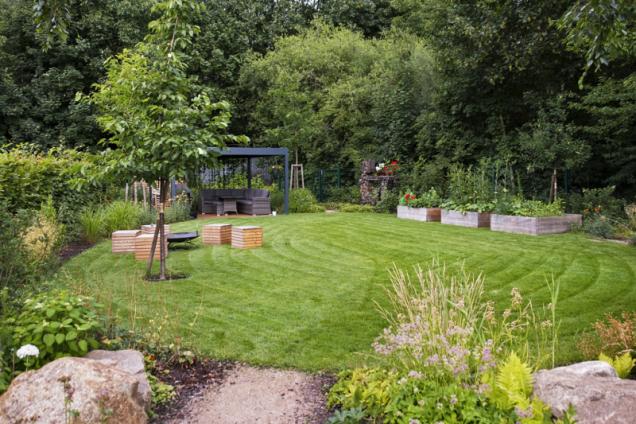 Pohled od domu směrem k pergole s grilem a posezením. Vpravo jsou vyvýšené zeleninové a bylinkové záhony, vlevo dřevěné kostky na sezení obklopující ohniště. Za pergolou se ukrývá malá travnatá plocha s kompostérem
