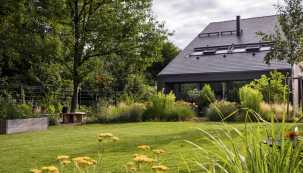 Pohled od pergoly s grilem přes víceúčelovou travnatou plochu s kovovým ohništěm (vpravo) směrem k domu. Za nízkou bariérou z keřů a trvalek se ukrývá terasa u domu. Vlevo obklopuje kmen vzrostlého stromu originální kulatá dřevěná lavice, která nabízí jedno z mnoha míst k posezení na zahradě
