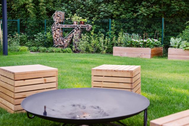 Od ohništi se nabízí pohled na kovovou sochu Jakuba Flejiara, která nejen dotváří srdečnou atmosféru zahrady, ale navíc je i funkční: nabízí blízký zdroj dřeva pro ohništi