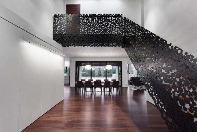 Přízemí s výhledem na zahradu a schodištěm v černé železné krajce udává ráz celému domu.