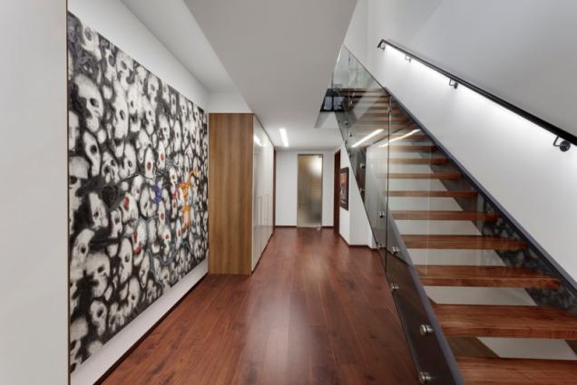 Vedle garáže se nachází schodiště ze dřeva a oceli se skleněnou zástěnou vedoucí do pokoje pro hosty a do suterénu se společenskou místností, koupelnou a domácí tělocvičnou.