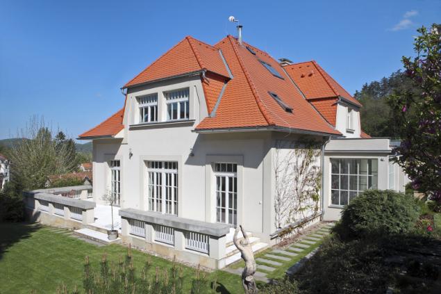 Přistavěná část domu výškově přímo navazuje na úroveň zahrady. Je ze tří stran obklopena terasou s typickým prvorepublikovým zábradlím