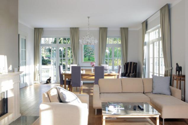 Společný obývací prostor je krásně prosvětlen a propojen s terasou řadou francouzských oken s charakteristickými tabulkami. Vzorově minimalizované závěsy pak dodávají prostoru autentickou útulnost. Barevné ladění obývací místnosti, stejně jako celého domu, demonstruje dobový přelom, kdy končila éra sytých, ostrých barev a nahradily je decentní odstíny v nenápadných akcentech bílé, šedé či olivové a celé škále hnědé