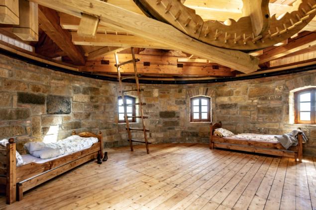 Poslední patro slouží jako hostinský pokoj s viditelným mlýnským mechanismem u stropu. Na spodním obrázku je detail hlavního hřídele s palečným kolem a brzdou