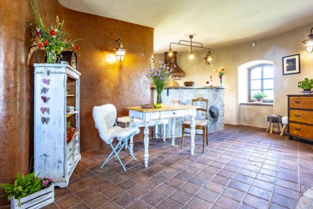 Stylově zařízená obývací místnost s kuchyní v přízemí větrného mlýna, kde se odehrává většina společenských akcí a setkání s přáteli