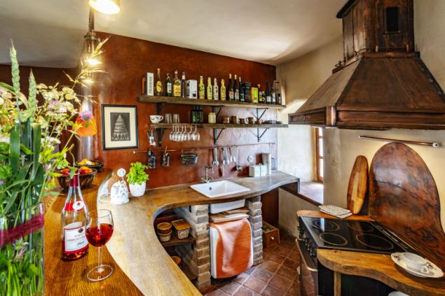 K prostorné obývací místnosti patří také kuchyně s obslužným pultem. Ani zde nechybí mistrně aranžované květiny