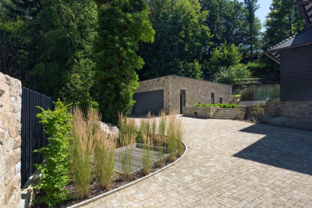 Vstup na pozemek a zpevněné plochy kolem domu byly nově upraveny, terasovitě uspořádány a vydlážděny žulou. Garáž postavená na místě té původní má zelenou střechu