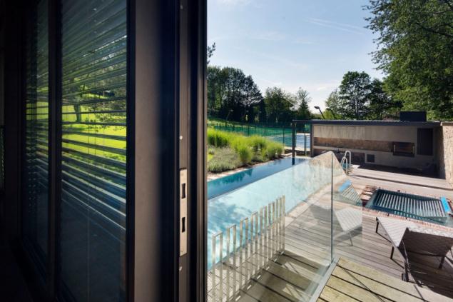 Do terasy z tropického dřeva je zapuštěn nerezový přelivový bazén 3,5 x 12 m a nerezová vířivka (dodavatel Berndorf Bäderbau). Zábradlí z čirého tvrzeného skla umožňuje přímý kontakt se zahradou i při koupání v bazénu