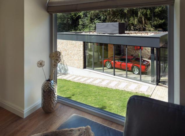 Původní dům komunikuje s novými objekty. Nové okno v obývacím pokoji bylo navrženo tak, aby poskytovalo přímý výhled na veterány vystavené v garáži