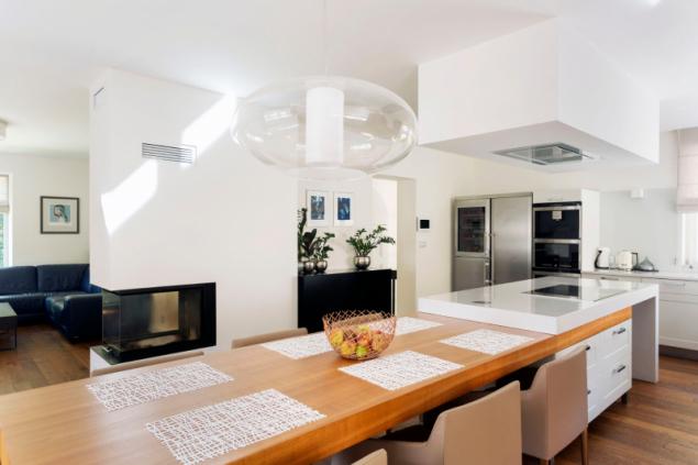 Obývací prostor v přízemí má tvar písmene L, od schodišťové haly jej odděluje pouze krbové těleso. Základem rodinného života je kombinace varného ostrůvku a dlouhého jídelního stolu. V sádrokartonovém podhledu je zapuštěna nerezová stropní digestoř. Vybavení interiéru podle návrhu architektů realizovala firma I+M Cípek z Rájce-Jestřebí