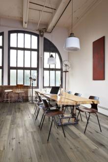 Industriální styl loftu s kovovými okny, přiznanými instalacemi a průmyslovými svítidly podtrhuje dubová podlaha s výraznou strukturou a jemnou patinou (podlaha KÄHRS, kolekce Domani, prodává síť KPP)